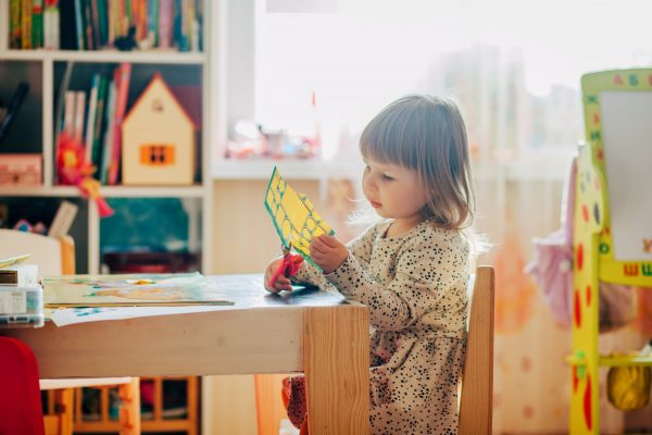 Young girl using scissors to cut paper