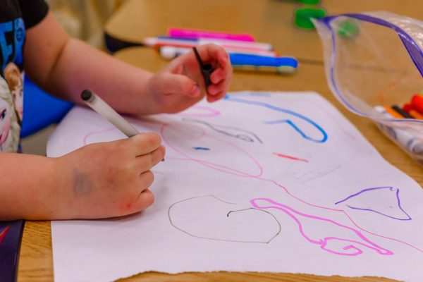Toddler drawing pre-writing strokes with markers